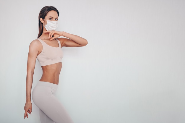 Portret van mooie jonge vrouw in sportkleding met beschermend masker