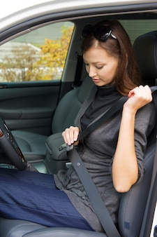 Portret van mooie jonge vrouw maakt een veiligheidsgordel in de auto vast