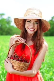 Portret van mooie jonge vrouw met bessen in het veld