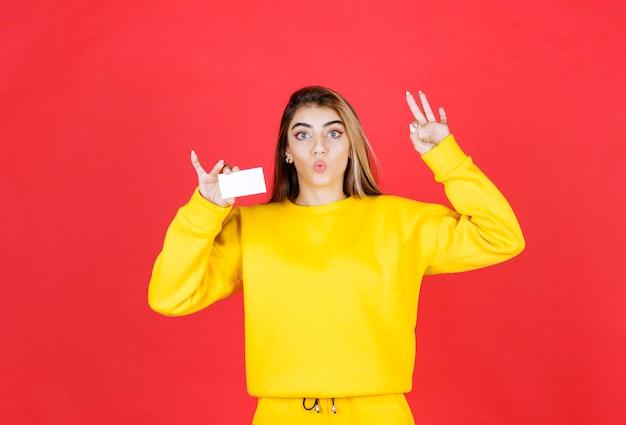 Portret van mooie jonge vrouw met blanco visitekaartje die ok teken geeft