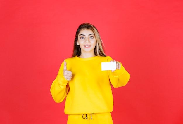 Portret van mooie jonge vrouw met blanco visitekaartje duimen opgevend