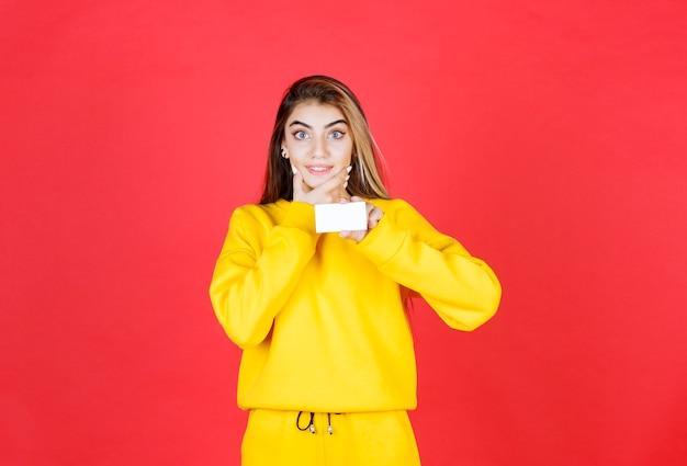 Portret van mooie jonge vrouw met blanco visitekaartje staan