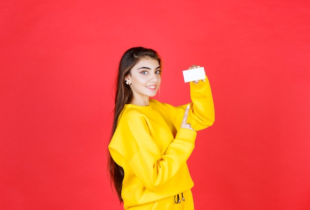 Portret van mooie jonge vrouw met blanco visitekaartje staande en poseren?