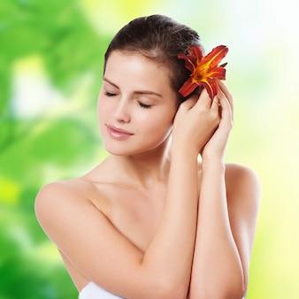Portret van mooie jonge vrouw met bloem in het haar