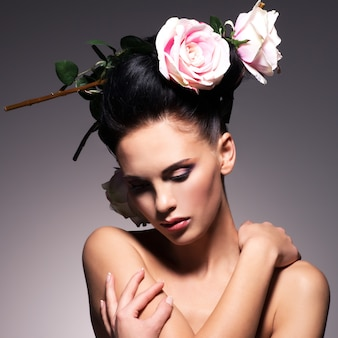 Portret van mooie jonge vrouw met bloemen in haar vormt