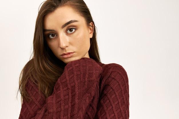 Portret van mooie jonge vrouw met bruin haar poseren geïsoleerd dragen warme gebreide trui, koud op winderige herfstdag.
