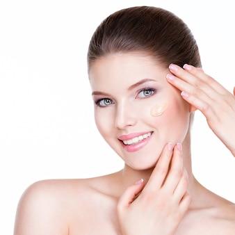 Portret van mooie jonge vrouw met cosmetische foundation op een huid - geïsoleerd op een witte achtergrond.