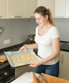 Portret van mooie jonge vrouw met dienblad met rauwe koekjes