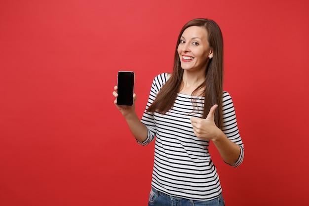Portret van mooie jonge vrouw met duim omhoog met mobiele telefoon met leeg zwart leeg scherm geïsoleerd op heldere rode achtergrond. mensen oprechte emoties, lifestyle concept. bespotten kopie ruimte.