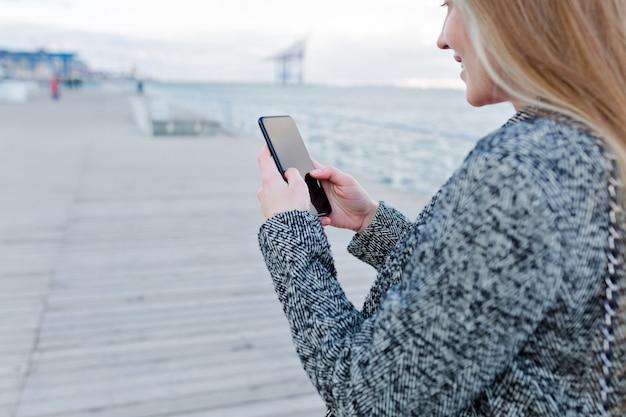 Portret van mooie jonge vrouw met een gelukkige glimlach in grijze vacht scrollen smartphone in de buurt van de zee