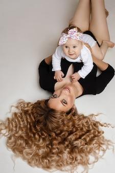 Portret van mooie jonge vrouw met eerlijk golvend haar op de vloer in zwart lichaam met haar dochtertje op haar buik in de armen en glimlachend in de camera.