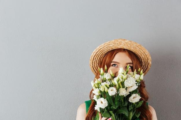 Portret van mooie jonge vrouw met gemberhaar die de hoed van de strohoed dragen van verbazende witte bloemeneustoma, die over grijze muur wordt geïsoleerd