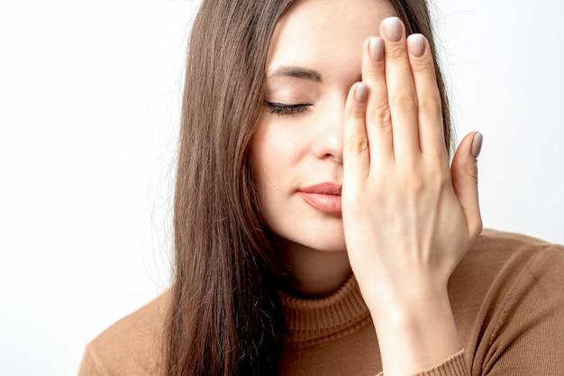 Portret van mooie jonge vrouw met gesloten ogen die één oog behandelen door haar hand