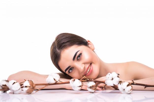 Portret van mooie jonge vrouw met gezondheidshuid en met bloem op haar geïsoleerde schouder