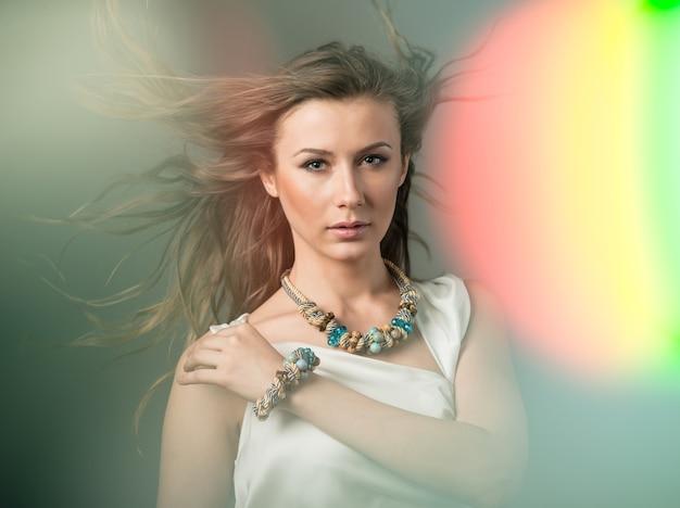 Portret van mooie jonge vrouw met groene ogen in enorme gebreide accessoires