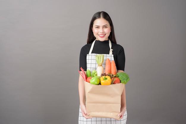 Portret van mooie jonge vrouw met groenten in boodschappen tas op studio grijze achtergrond