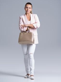 Portret van mooie jonge vrouw met handtas.