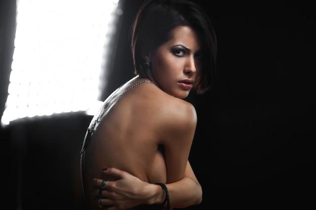 Portret van mooie jonge vrouw met juwelen op handen