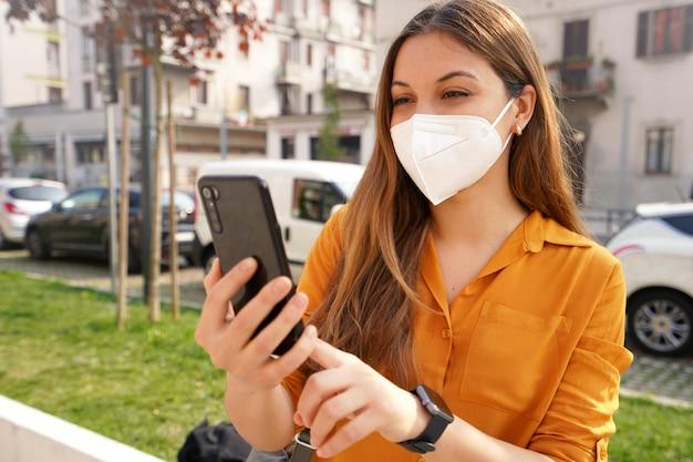 Portret van mooie jonge vrouw met kn95 ffp2 beschermend masker videobellen met mobiele telefoon buitenshuis