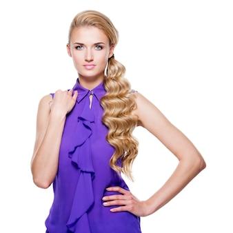 Portret van mooie jonge vrouw met lang blond krullend haar - dat op witte muur wordt geïsoleerd.