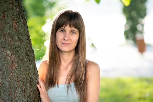 Portret van mooie jonge vrouw met lang haar staande nette boomstam in de zomer.