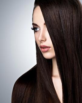 Portret van mooie jonge vrouw met lang steil haar in de studio