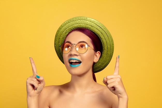 Portret van mooie jonge vrouw met lichte make-up geïsoleerd op geel