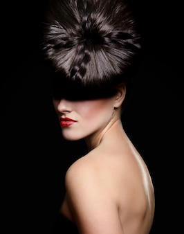 Portret van mooie jonge vrouw met rode lippen en ongebruikelijke kapsel met schaduw op ogen op zwarte achtergrond