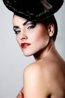 Portret van mooie jonge vrouw met rode lippen en ongebruikelijke kapsel op grijs