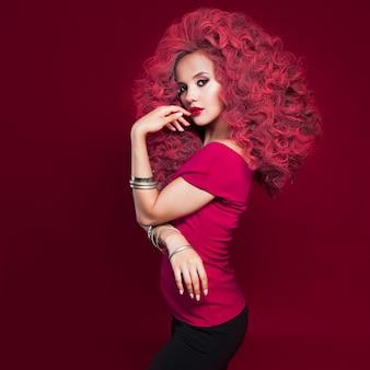Portret van mooie jonge vrouw met rood haar op rode muur