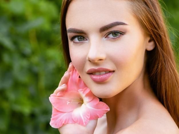 Portret van mooie jonge vrouw met schoon gezicht. mooi gezicht van jonge volwassen vrouw met schone huid - natuur. gezicht van de jonge mooie sexy vrouw buitenshuis. schoonheid gezicht met bloem.