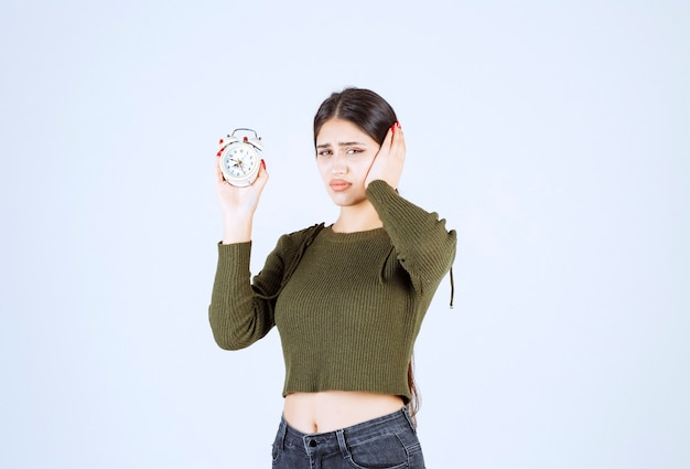 Portret van mooie jonge vrouw met wekker met gekke uitdrukking.