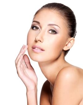 Portret van mooie jonge vrouw met zuivere gezonde huid die haar gezicht zachtjes aanraakt