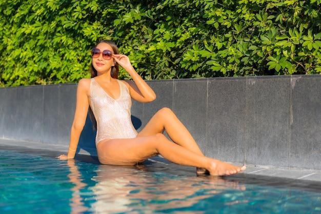 Portret van mooie jonge vrouw ontspannen bij het zwembad