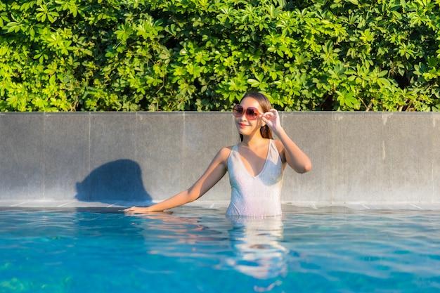 Portret van mooie jonge vrouw ontspannen bij het zwembad Gratis Foto