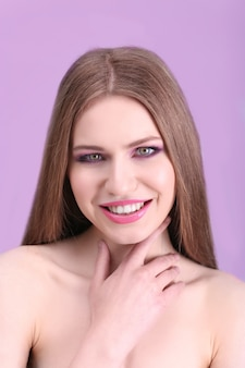 Portret van mooie jonge vrouw op kleur oppervlak