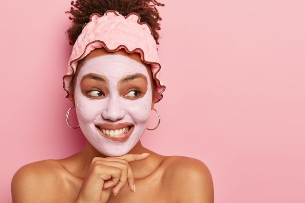 Portret van mooie jonge vrouw raakt kin, heeft een zachte brede glimlach, past kleimasker toe voor verjonging, staat blote schouders tegen roze muur