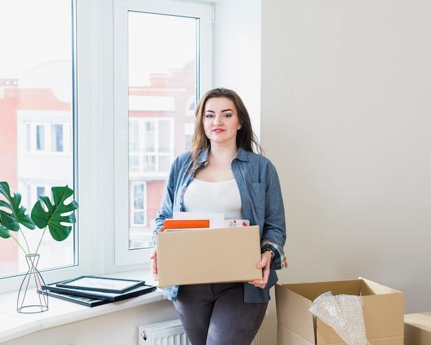 Portret van mooie jonge vrouw uitpakkende kartonnen dozen bij haar nieuwe huis