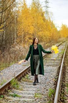 Portret van mooie jonge vrouw van slavische verschijning in donkere jurk in de herfst, gelegen in bos met spoorweg