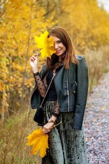 Portret van mooie jonge vrouw van slavische verschijning in donkere jurk in de herfst, staande tegen de achtergrond van een herfstpark met bladeren in haar handen