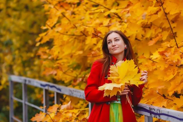 Portret van mooie jonge vrouw van slavische verschijning in geel gekleurde jurk en rode jas in de herfst, wandeling in het bos. schattig model loopt in het park in de gouden herfst tegen de achtergrond van de natuur