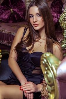 Portret van mooie jonge vrouw zitten, poseren en kijken naar de camera.