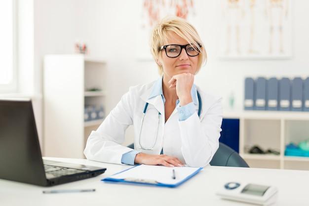 Portret van mooie jonge vrouwelijke arts in bureau