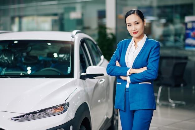 Portret van mooie jonge vrouwelijke dealer manager permanent naast auto, armen vouwen en camera kijken