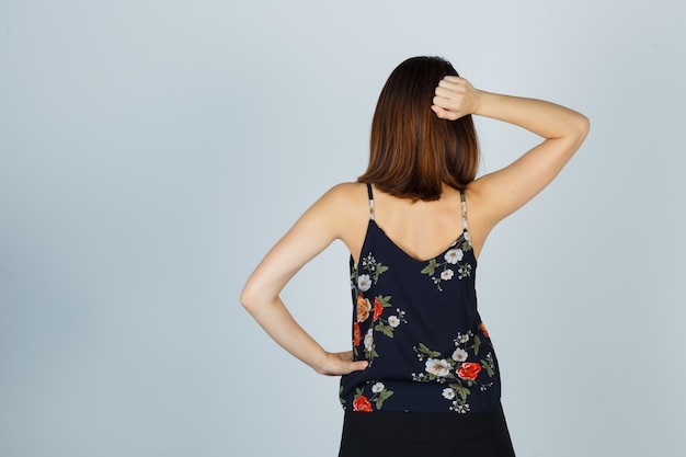 Portret van mooie jonge vrouwelijke holdingshand achter hoofd in blouse