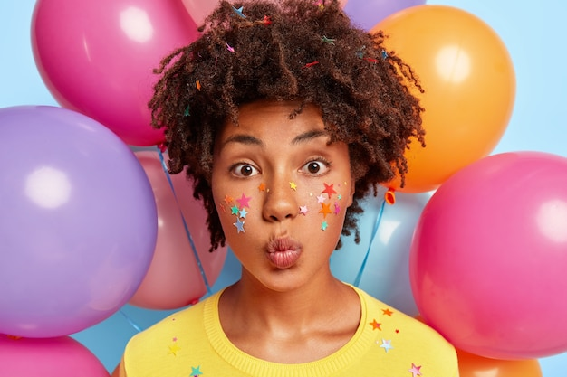Portret van mooie jonge vrouwelijke model met krullend kapsel, houdt de lippen gevouwen, kleeft kleurrijke sterren op het gezicht, draagt gele kleding, maakt grimas, bos helium-luchtballonnen in muur