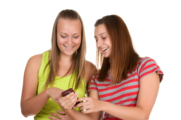 Portret van mooie jonge vrouwen die mobiele telefoon met behulp van die samen op wit wordt geïsoleerd