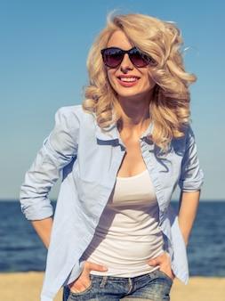 Portret van mooie jonge vrouwenglimlach op strand.
