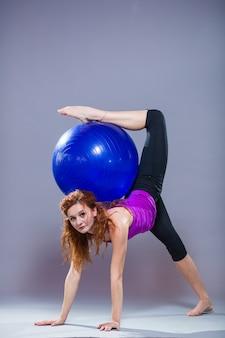 Portret van mooie jonge vrouwensportkleding die op grijze achtergrond uitwerkt. fit sportief meisje doet geavanceerde yoga, pilates, fitness.