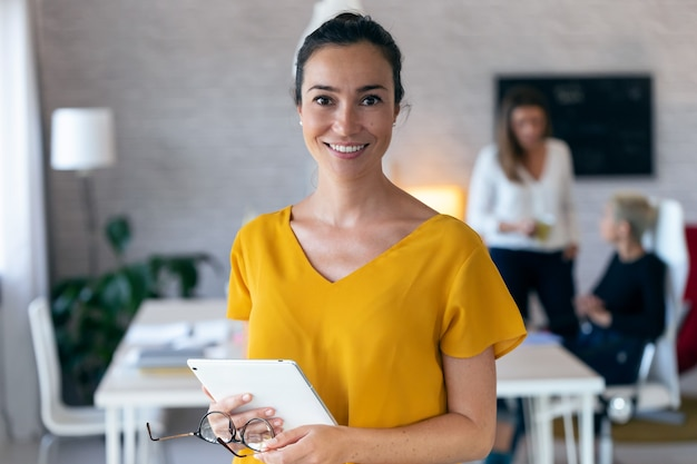 Portret van mooie jonge zakenvrouw camera kijken. op de achtergrond werken haar collega's op kantoor.
